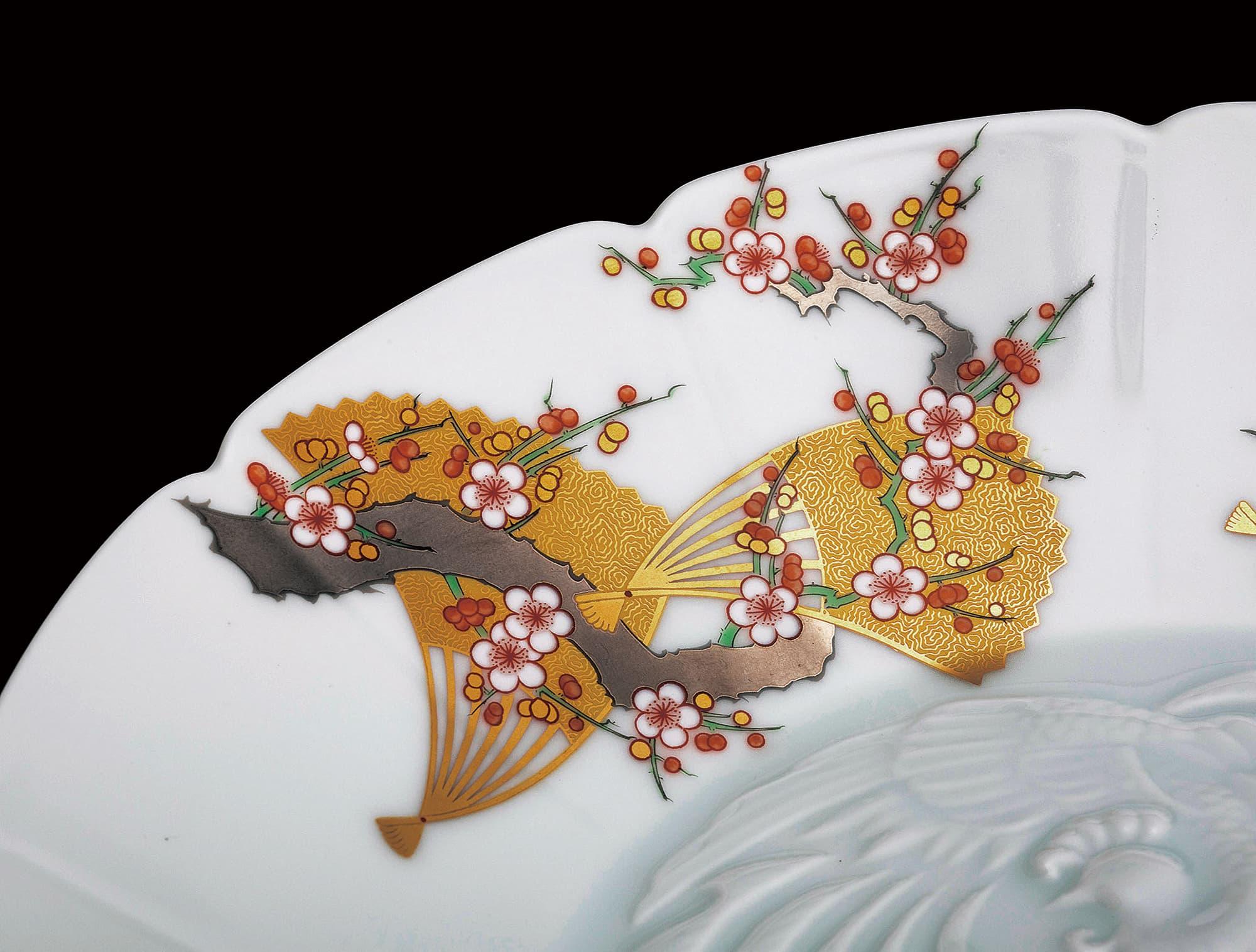 金彩折扇与红梅白梅、嫩绿枝桠绝妙地搭配在一起。铂金树枝低调的光芒象征了日本的审美观。