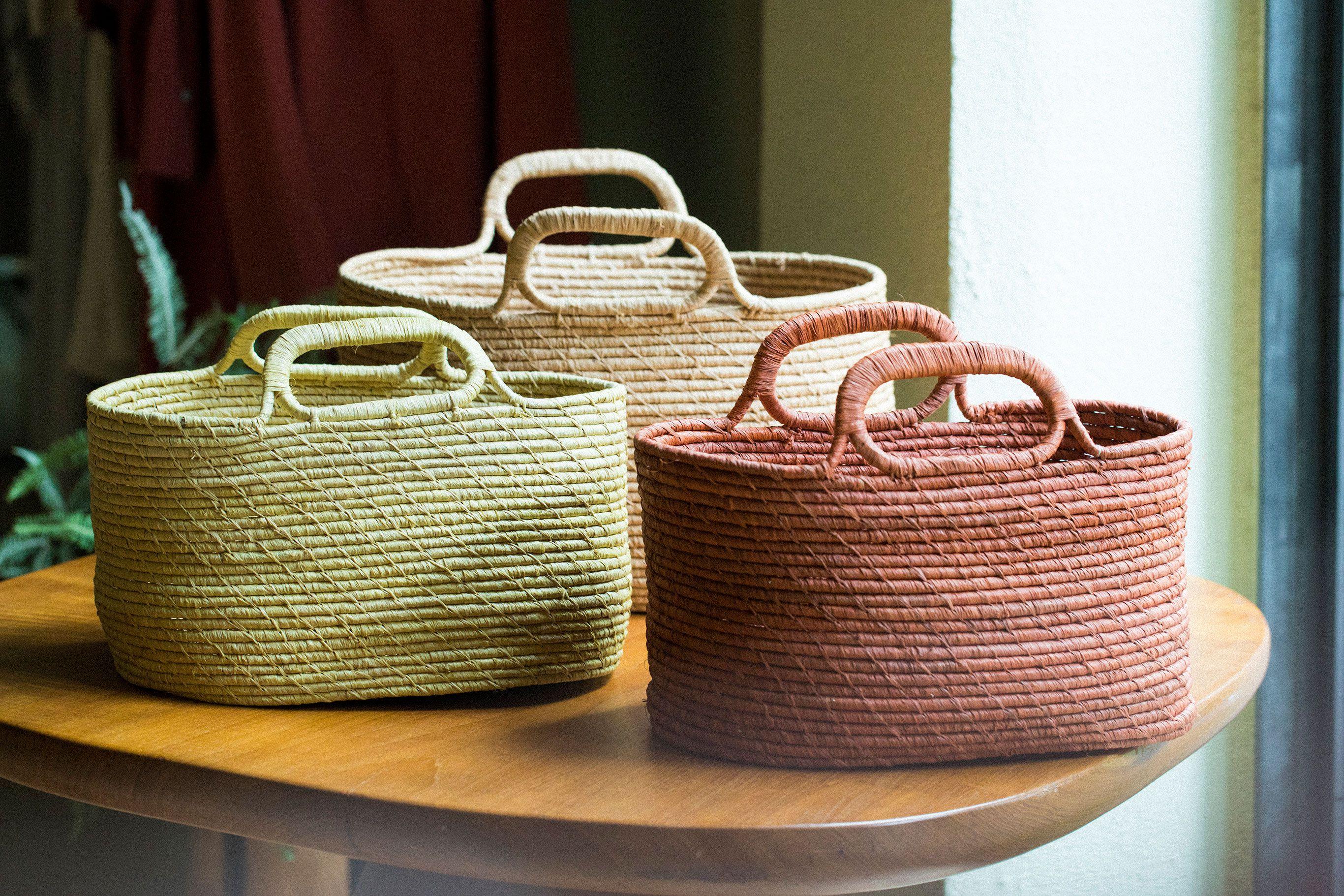 ラフィアのコイル編みのカゴはマダガスカル産。夏らしい色味のカゴで季節を楽しむ。小12,960円 大16,200円(どちらも税込)