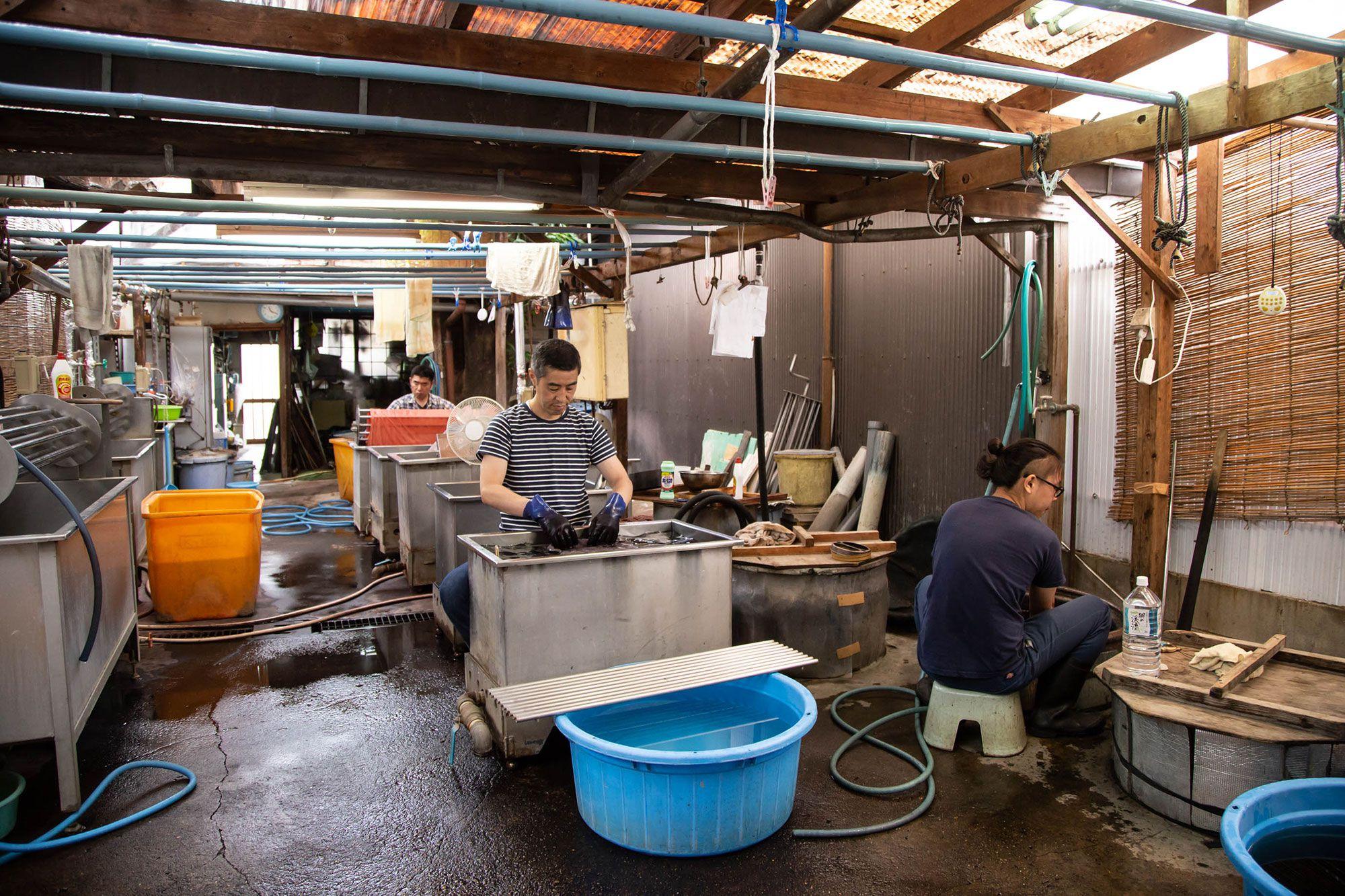 工房の内部。右の人は木綿の藍染めを、手前の人は絹を、奥の人は大きな木綿を染めていた。