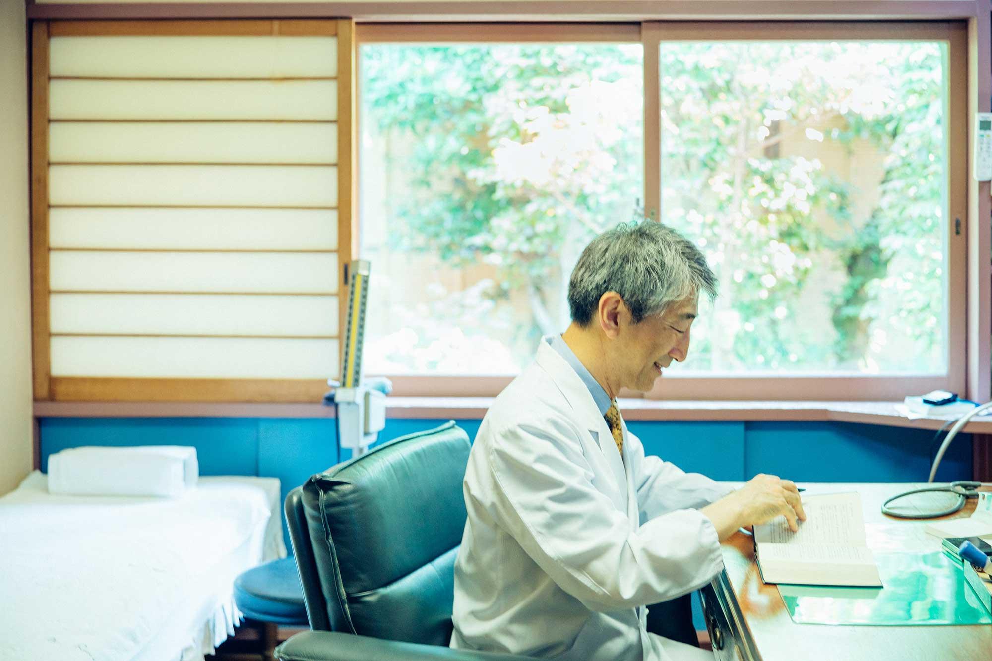 診察室の渡辺院長。大きな窓から庭の緑が見える診察室は、安らげる雰囲気がある。初診の人には、時間をかけて話を聞くという。