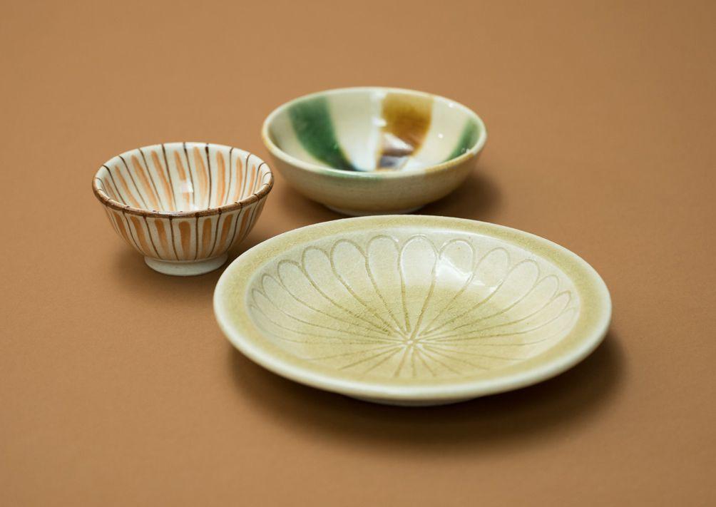 瀬戸本業窯/(奥から)三彩スープ鉢、麦藁手茶碗、黄瀬戸石皿。瀬戸本業窯は、瀬戸で約300年続く窯元。民藝の思想に基づき、瀬戸焼の制作、販売を行う。