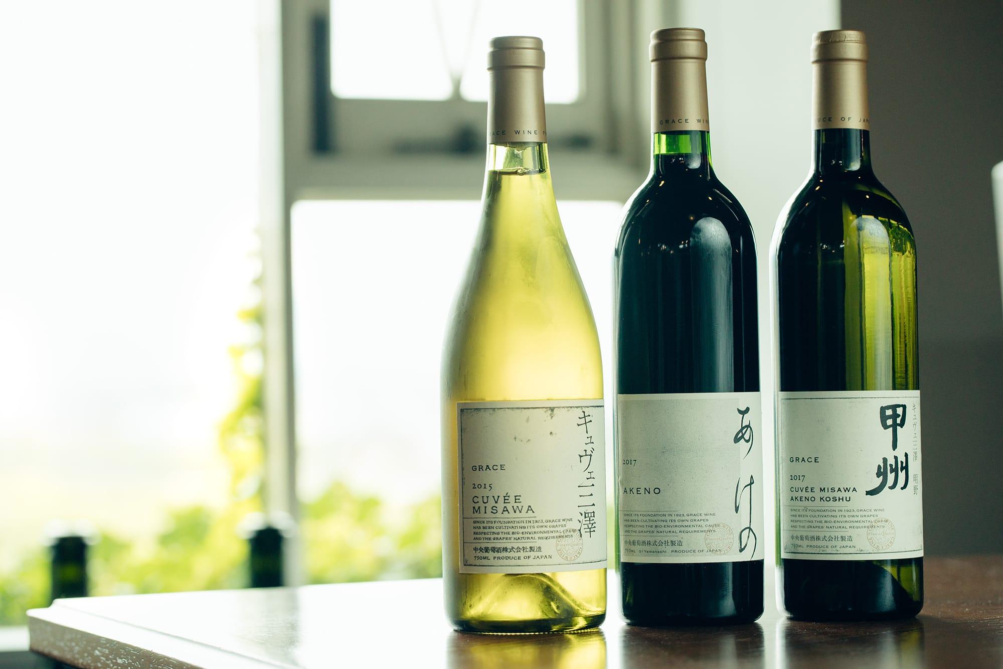 (右)2014年のDWWAで金賞を受賞したものと同じ「キュヴェ三澤 明野甲州」。(中央)新登場の「あけの」。現在、赤ワインは品種よりも産地の個性を表現する方向で、三澤農場の最高峰「キュヴェ三澤」のセカンドラベルの役割を果たす。メルロー、カベルネ・ソーヴィニヨン、カベルネ・フラン、プティ・ヴェルドをブレンドした、ボルドースタイルの赤。(左)90年代から高い評価を得る「キュヴェ三澤」の白。シャルドネ100パーセント。全てラベルデザインはグラフィックデザイナーの原研哉によるもの。