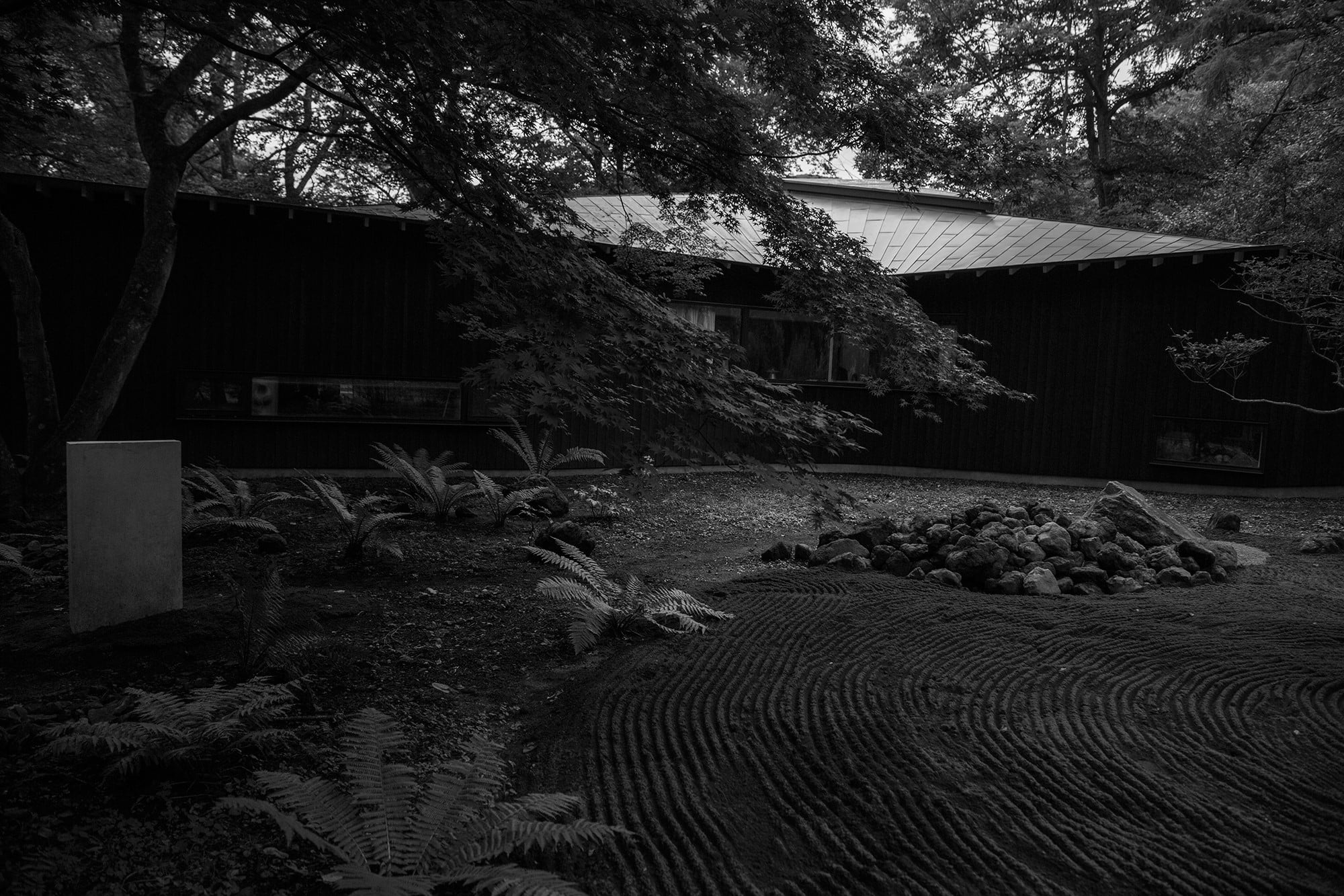 庭にはこの土地の岩を置き、黒い枯山水をつくった。日本の庭への思いは自然の模倣からはじまった。