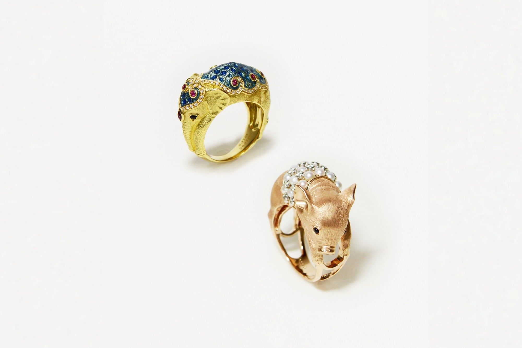 写真左 祭りのための衣装をつけた「ゾウ」リング。K18イエローゴールド・ダイヤモンド・ルビー・エナメル・オニキス。¥1,560,000、 写真右 真珠のタンクトップを着た「ブタ」リング。K18ピンクゴールド・プラチナ・ダイヤモンド・アコヤ真珠・オニキス。¥1,950,000 ともに税別