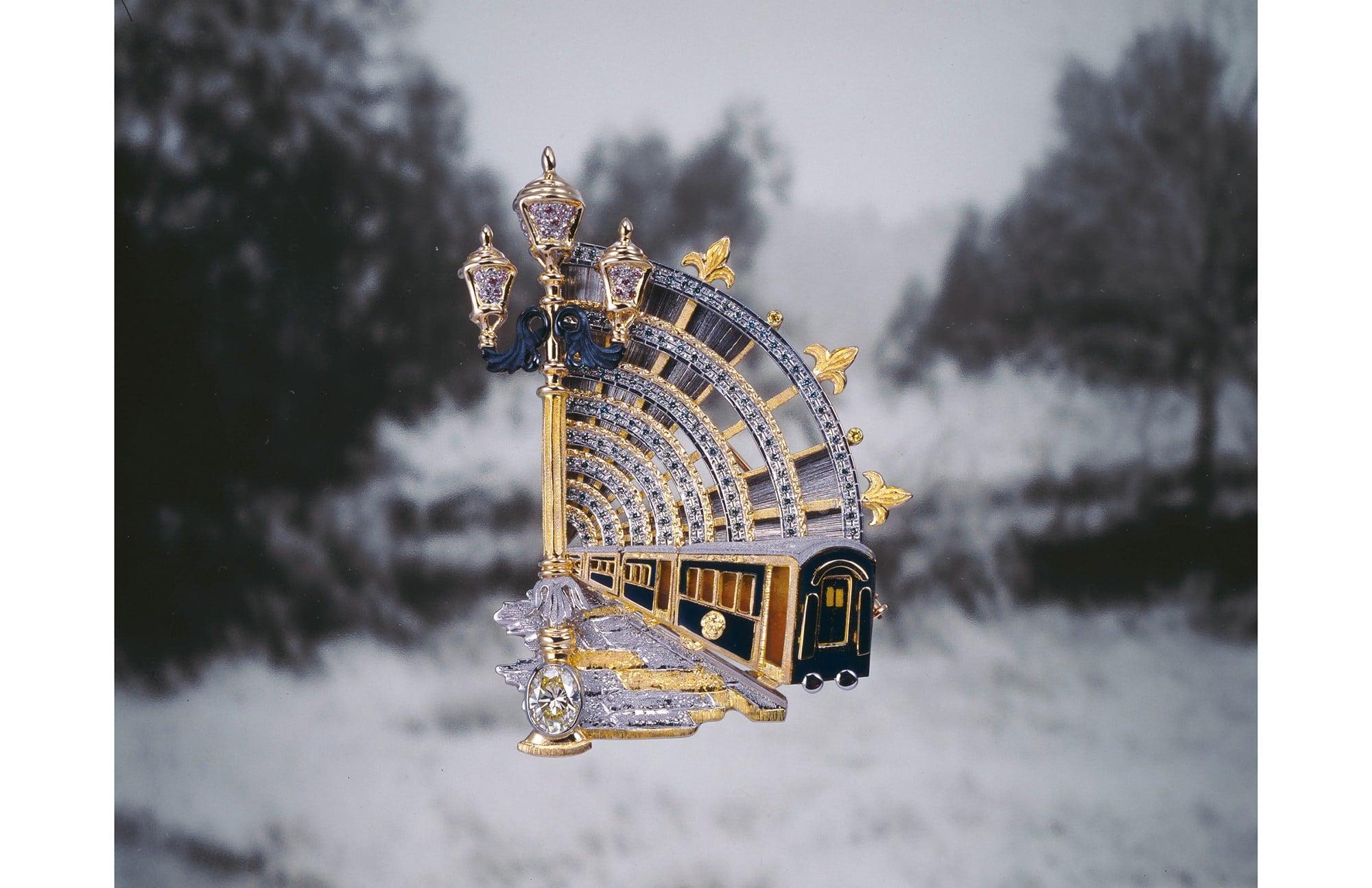 「ヨーロッパ城紀行」シリーズ。2つの都市をつなぐオリエント急行を題材に、列車、ベニスのガス燈や石畳、パリ・オルセー駅のアールデコ様式のドームを描写している。旅情を誘う作品。 「ベニスからパリへ」プローチ/ペンダント。K18イエローゴールド・Pt900・ダイヤモンド・赤銅・七宝。6,700,000円 税別(参考上代)