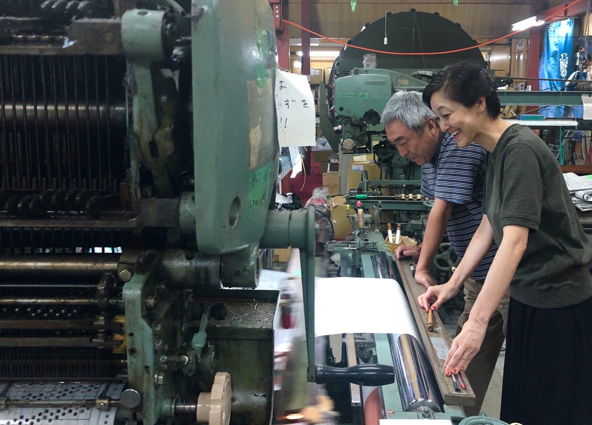 山梨の機屋さんの工房で、たて糸を作る様子を見る瀬口。「私の要求に快く応じてくださり、さらにイメージをふくらませてくれる職人さんとの交流が私のモチベーションの源です」。