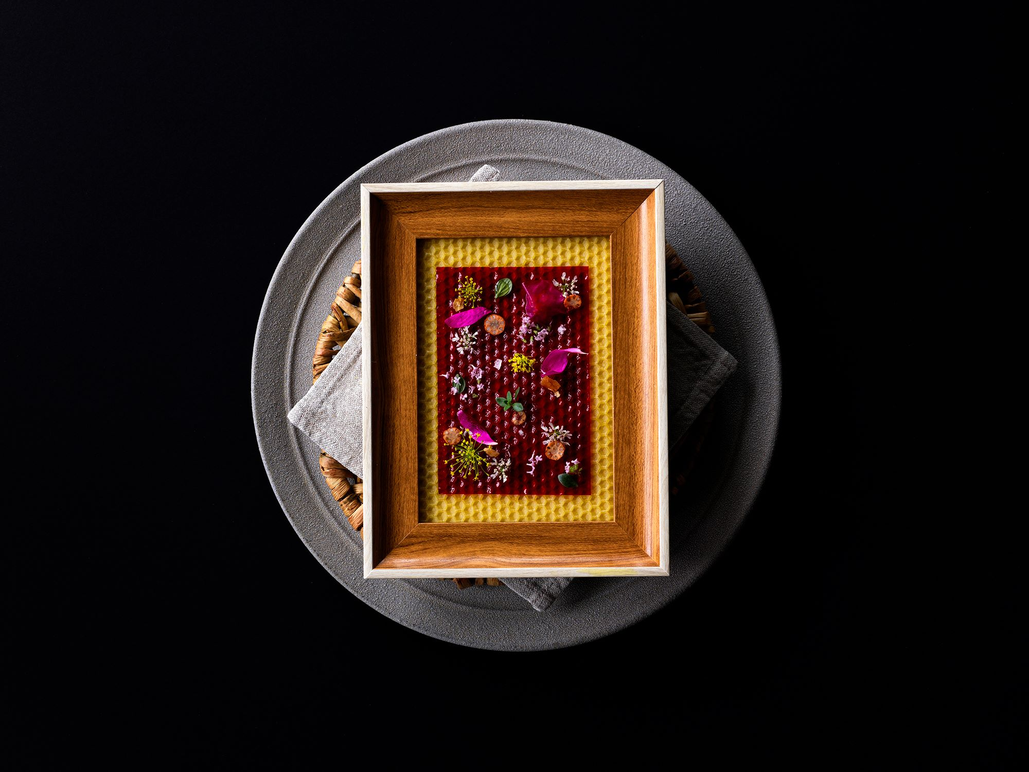"""""""The Plum leather with fresh aromatic flowers"""" clearly represents the fascination of INUA. The edible flowers and herbs are arranged on the sheet made of plum juice, and afterwards placed over the beeswax.  Photography Jason Loucas"""